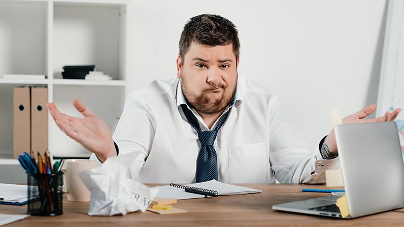 Ein Mann sitzt ratlos am Schreibtisch vor dem Laptop.