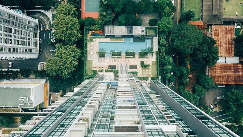 Der Blick geht von einem Hochhausdach hinunter zu einem Pool.