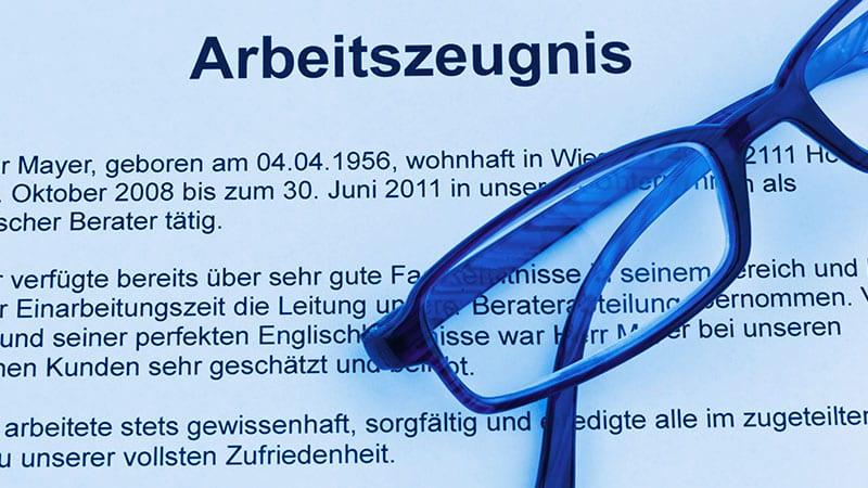 Eine Brille liegt auf einem Arbeitszeugnis, von dem der obere Teil des Textes lesbar ist.