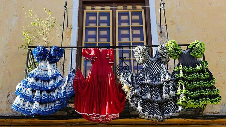 Vor einem spanischen Haus hängen mehrere traditionelle Flamenco-Kleider.