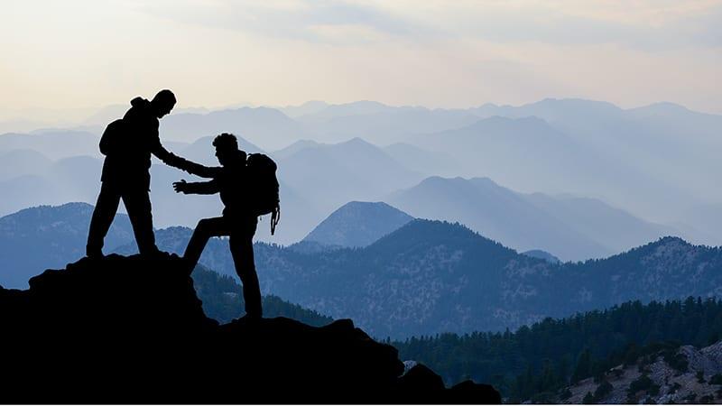 Ein Bergsteiger hilft einem zweiten, einen Gipfel zu erklimmen.