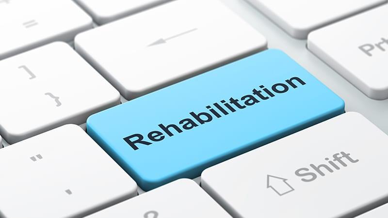 Auf einer Tastatur steht auf einer Taste das Wort Rehabilitation.