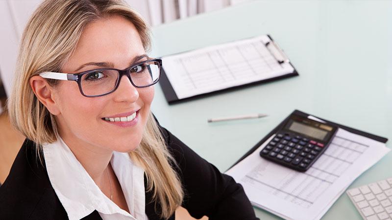 Eine Mitarbeiterin sitzt vor Tabellen und einem Taschenrechner.