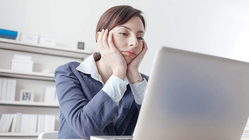 Eine Geschäftsfrau stützt den Kopf auf die Hände und blickt gelangweilt in den Laptop.