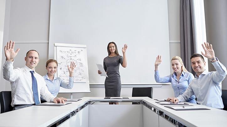Geschäftsleute im Meetingraum winken freundlich lachend.
