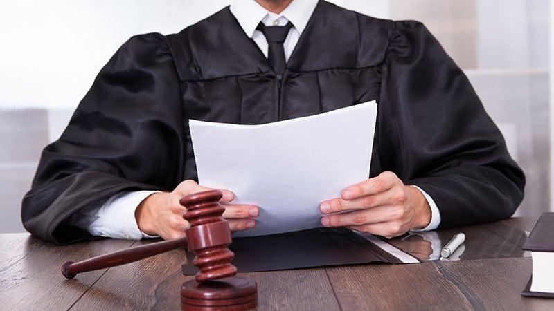 Ein Richter sitzt mit Papier-Unterlagen in den Händen am Tisch, vor ihm der Richterhammer.