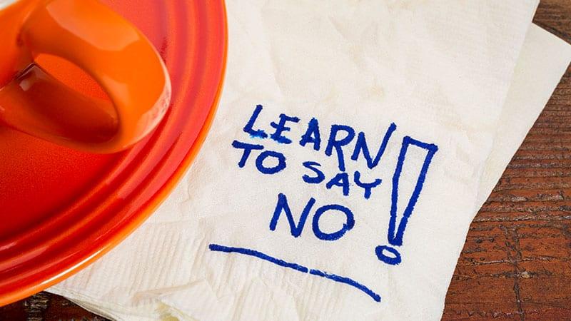 Auf einer Serviette neben einer roten Tasse steht Learn to say no!
