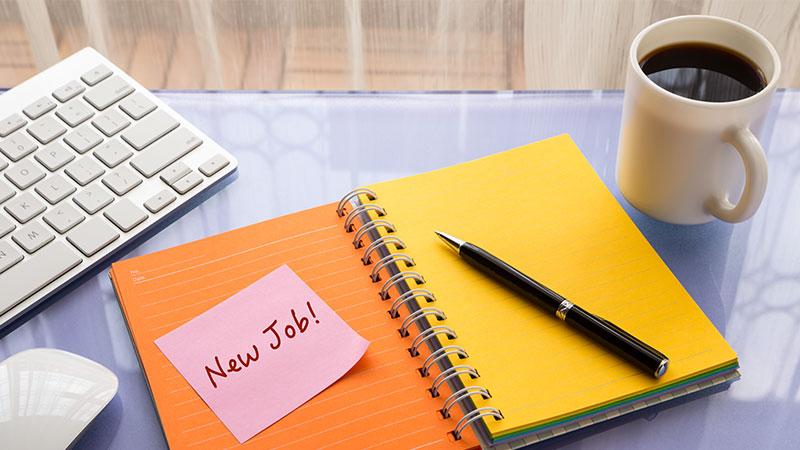 """Auf einem Schreibtisch liegen Block, Stift, Maus und Tastatur bereit; auf einem Zettel steht """"New Job!""""."""