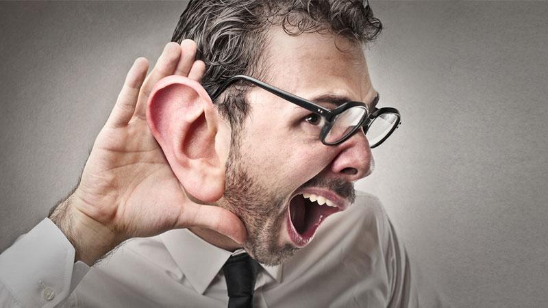 Ein Mann stellt sein überdimensionales Ohr auf, um besser zu hören.