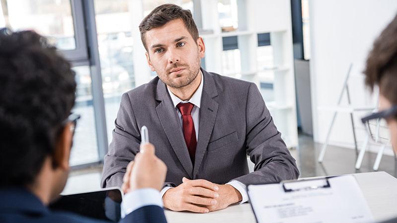 Zwei Interviewer befragen im Einstellungsgespräch einen Bewerber im Anzug; der eine studiert die Unterlagen, der andere zeigt mit einem Stift auf den Bewerber.