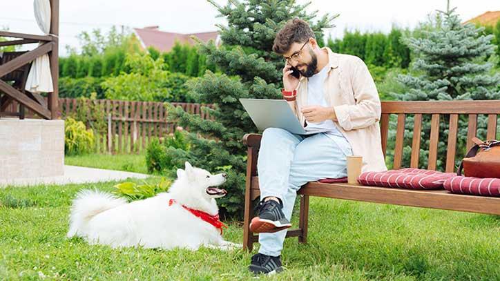 Ein Mann sitzt mit Laptop und Handy am Ohr auf einer Gartenbank im Grünen.