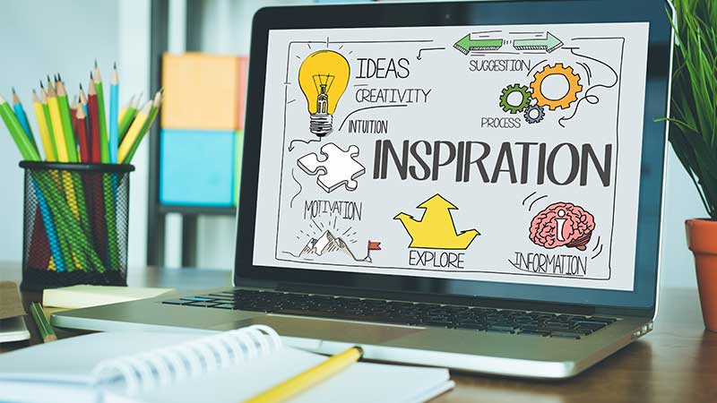 Ein Laptop-Bildschirm zeigt Worte wie Inspiration, Ideen, Kreativität, Motivation mit passenden Illustrationen