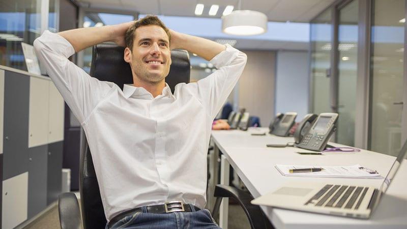 Ein Mann im Büro lehnt sich entspannt zurück.