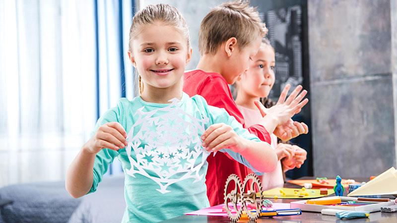 Drei Kinder basteln und ein Mädchen zeigt lachend ihr Ergebnis.