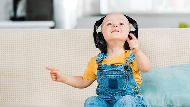 Ein Kind sitzt mit Kopfhörer auf dem Sofa und lacht.