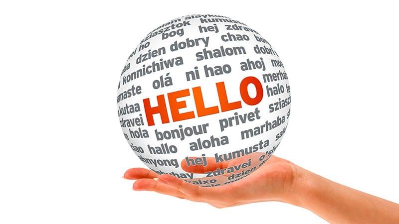 """Auf einer Hand liegt eine Blase, auf der """"Hello"""" in verschiedenen Sprachen steht."""