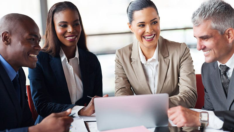 Geschäftsleute unterschiedlicher Herkunft sitzen lächelnd beim Meeting zusammen.