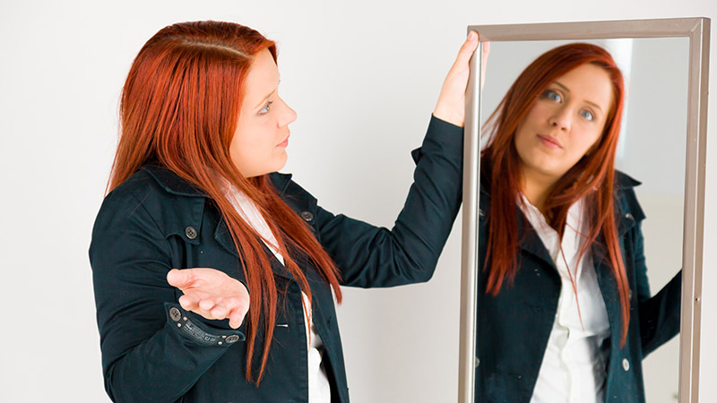 Eine Frau schaut sich fragend im Spiegel an.