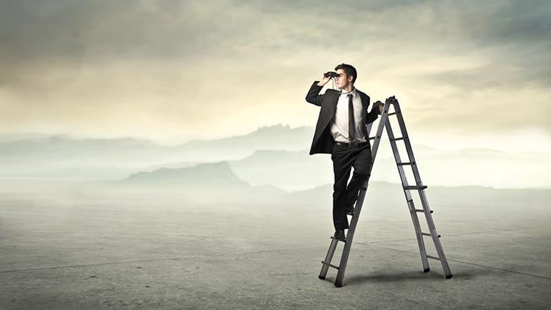 Ein Geschäftsmann auf einer Klappleiter schaut durch ein Fernglas in die Landschaft.