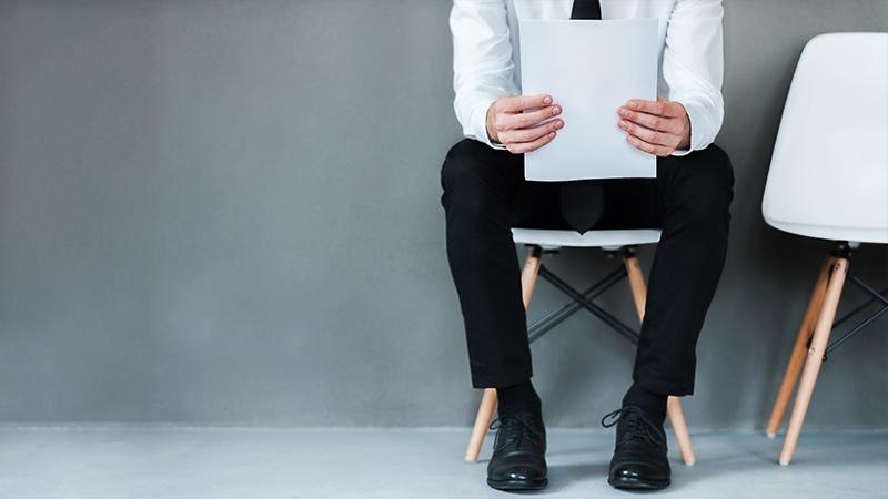 Ein Mann mit Bewerbungsschreiben sitzt wartend auf einem Stuhl.