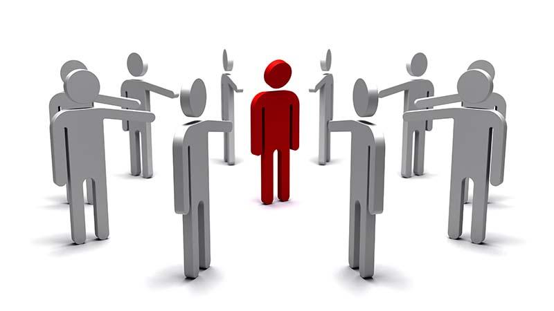 Eine Gruppe von Menschen zeigt auf eine einzelne Person in der Mitte.