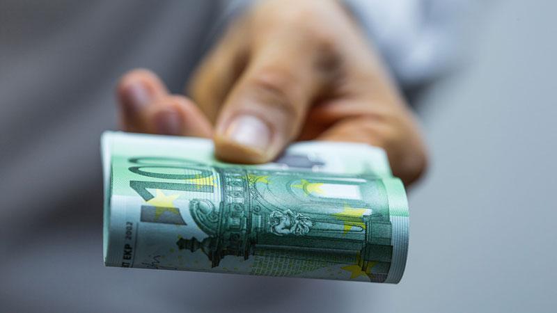 Eine Hand reicht einen Bündel Hundert-Euro-Scheine.
