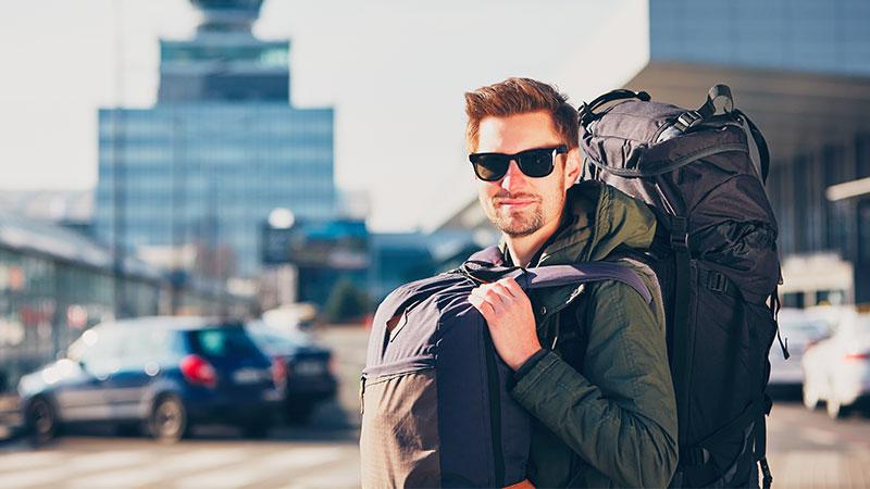 Ein Reisender mit Sonnenbrille und zwei großen Rucksäcken steht voller Vorfreude am Flughafen.