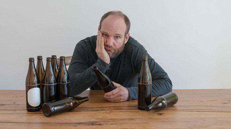 Ein Mann am Tisch mit leergetrunkenen Bierflaschen stützt sich niedergeschlagen auf.