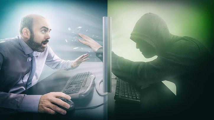 Eine dunkle Person mit Kapuzenpulli greift durch den Bildschirm am Computer-Arbeitsplatz eines Geschäftsmanns.