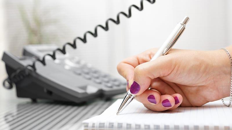 Vor einem Telefon schreibt eine Frauenhand auf einen Block.