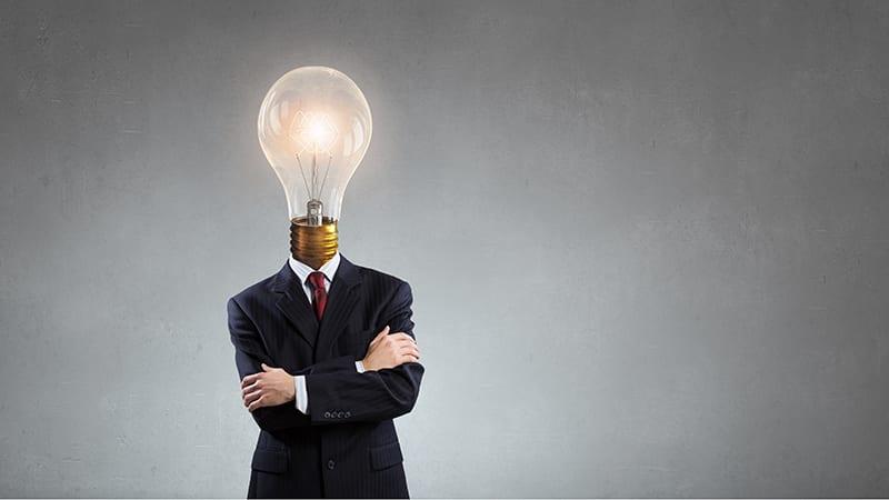 Ein Geschäftsmann hat als Kopf eine leuchtende Glühbirne.