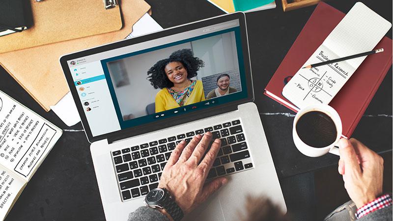 Ein Mann am Schreibtisch sieht über den Laptop zwei Kollegen in der Videokonferenz.