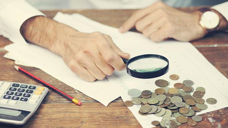 Ein Mann schaut mit einer Lupe über Papiere, verstreut liegen viele Münzen.