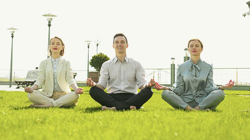 Drei Geschäftsleute sitzen nebeneinander im Schneidersitz auf der grünen Wiese und meditieren.