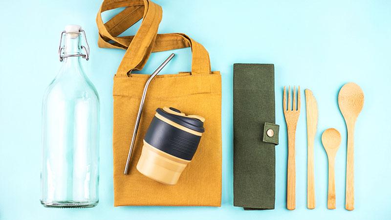 Aufgereiht sind eine Glasflasche, ein Jutebeutel, ein Metall-Strohhalm, ein Becher und Holzbesteck.