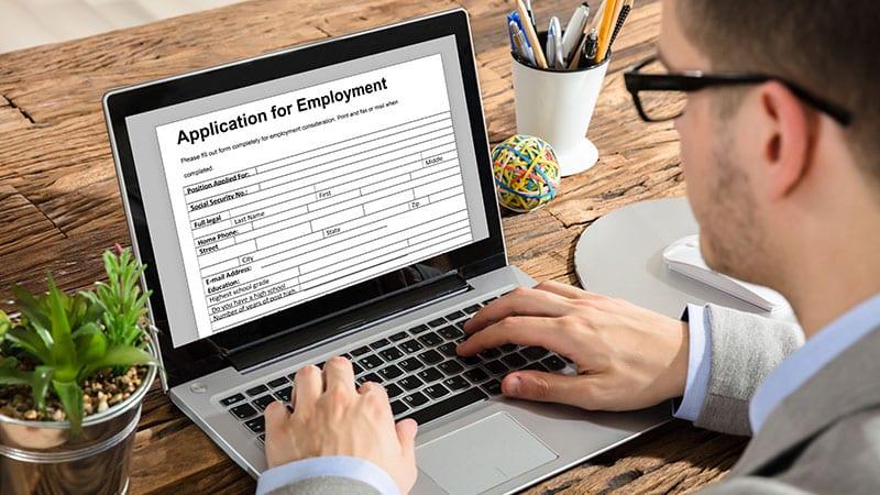 """Ein Mann sitzt am Schreibtisch vor einem Laptop und schreibt """"Application for Employment""""."""