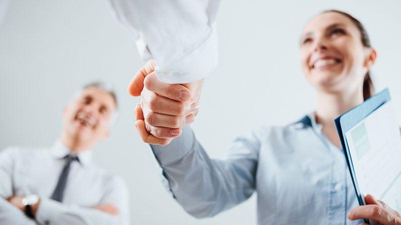 Aufnahme eines Handschlages zwischen einer Frau und einer anderen Person, aufgenommen von unten.