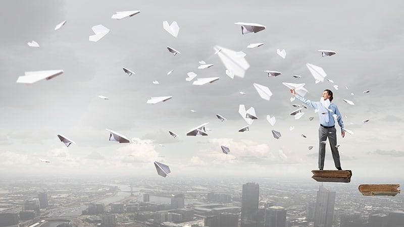 Ein Mann steht auf einer schwebenden Fläche in der rechten Ecke des Bildes und lässt viele Papierflugzeuge fliegen