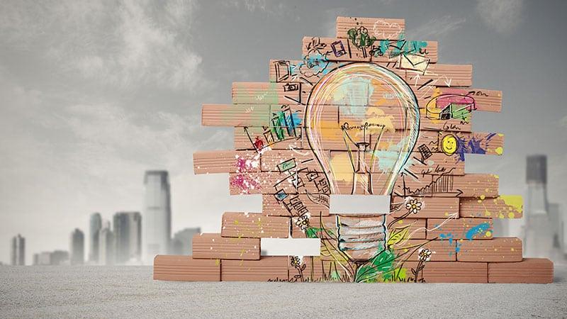 Eine Zeichnung, die eine kleine Mauer aus Backsteinen darstellt. Darauf ist ein farbiges Graffiti und die Silouette einer Glühbirnge