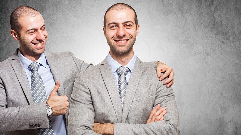 Ein Geschäftsmann legt den Arm um seinen Zwilling und zeigt mit dem Daumen nach oben.