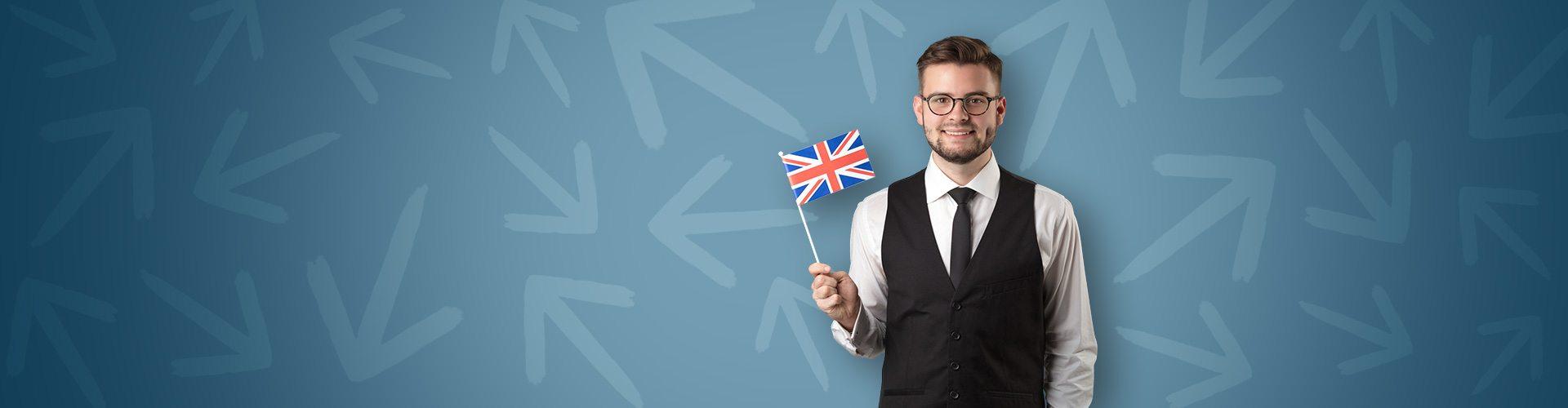 Mann vor blauem Hintergrund mit Pfeilen hält ein britisches Fähnchen in der Hand