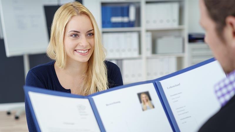 Eine Bewerberin lächelt ihren Gesprächspartner an, der gerade ihre Unterlagen studiert.