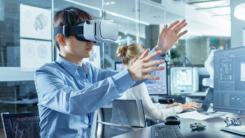 Ein Mann mit VR-Brille sitzt in einem futuristischen Büro und gestikuliert mit den Armen.