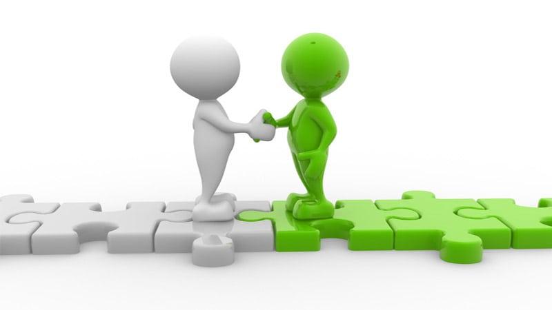 Zwei Männchen, weiß und grün, treffen sich in der Mitte eines Weges aus Puzzlestücken und geben sich die Hand.