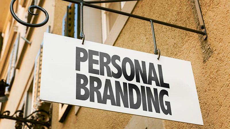 """Ein Schild mit """"Personal Branding"""" hängt vor einem Haus."""