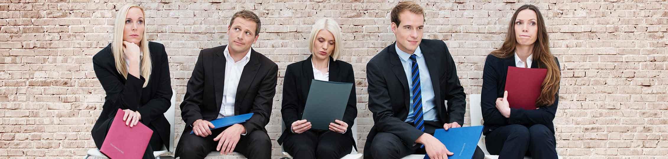 5 Bewerberinnen und Bewerber warten mit ihren Unterlagen auf das Vorstellungsgespräch