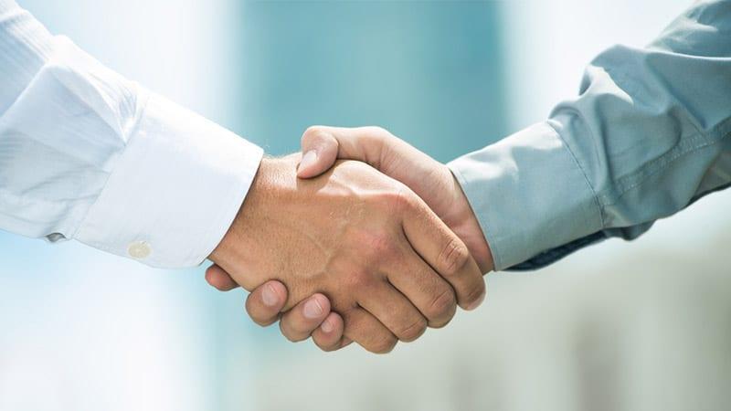 Zwei Geschäftsleute geben sich die Hand.
